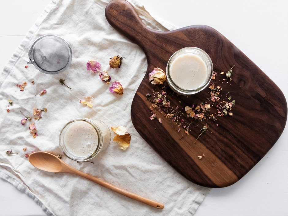 overhead image of a two glasses of rose milk, a tea strainer and wood cutting board.