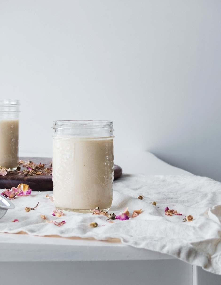 portrait image of a glass of rose milk in the forgeound and another one on a cutting board in the background.