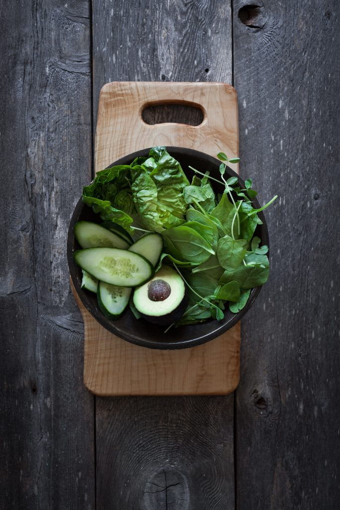 overhead view of fresh green vegetables in a bowl on a cutting board.