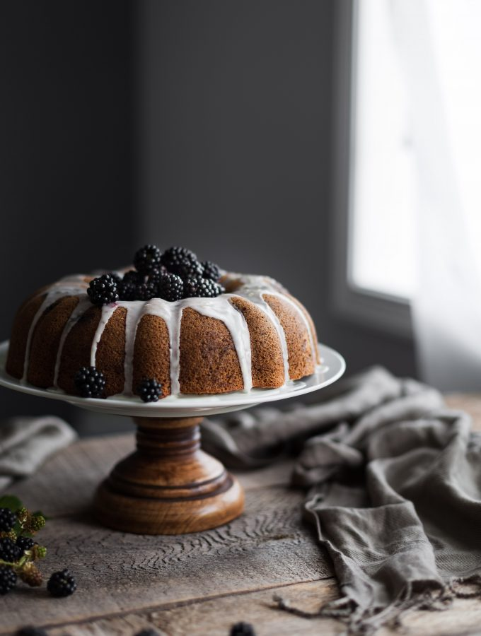a head on image of a blackberry bundt cake sitting by window