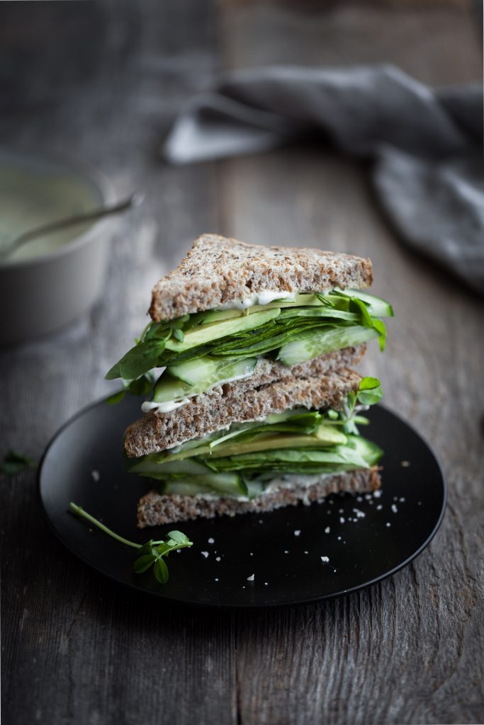 angled view of a green goddess sandwich stack on a black plate.
