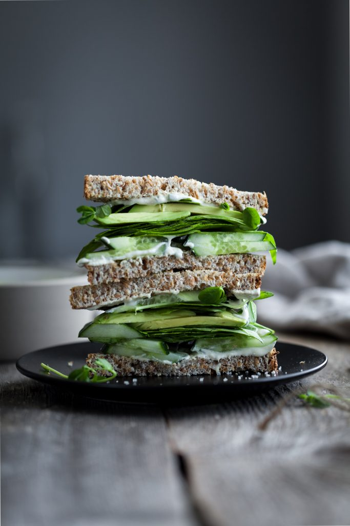 portrait view of a green goddess sandwich stack on a black plate.