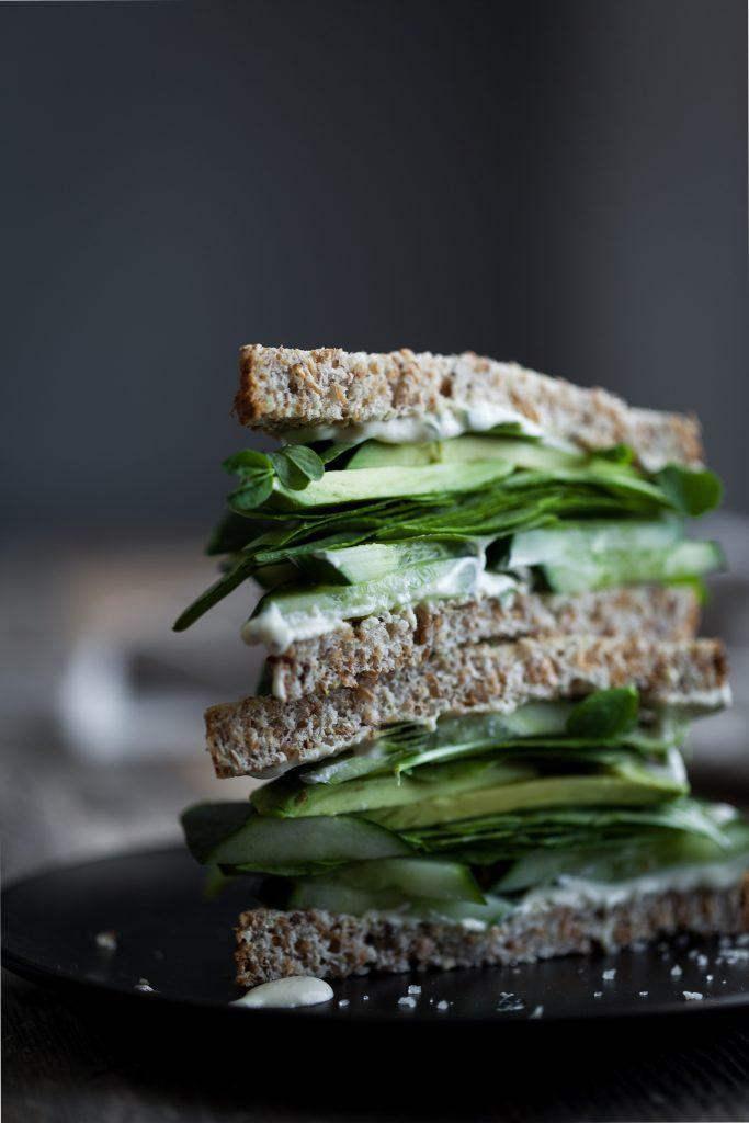 close up portrait of a vegan green goddess sandwich on a black plate.