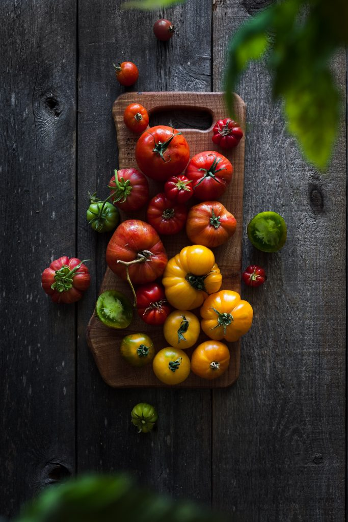 overhead view of heirloom tomatoes on a cutting board.
