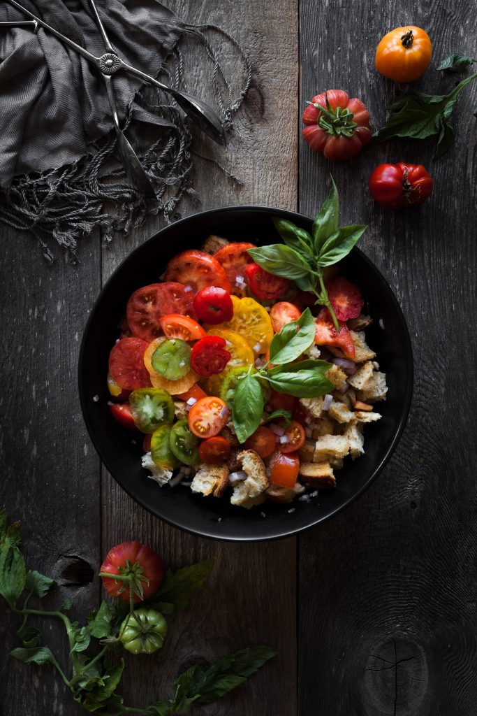 overhead view of tomato panzanella salad with tomatoes and basil leaves.