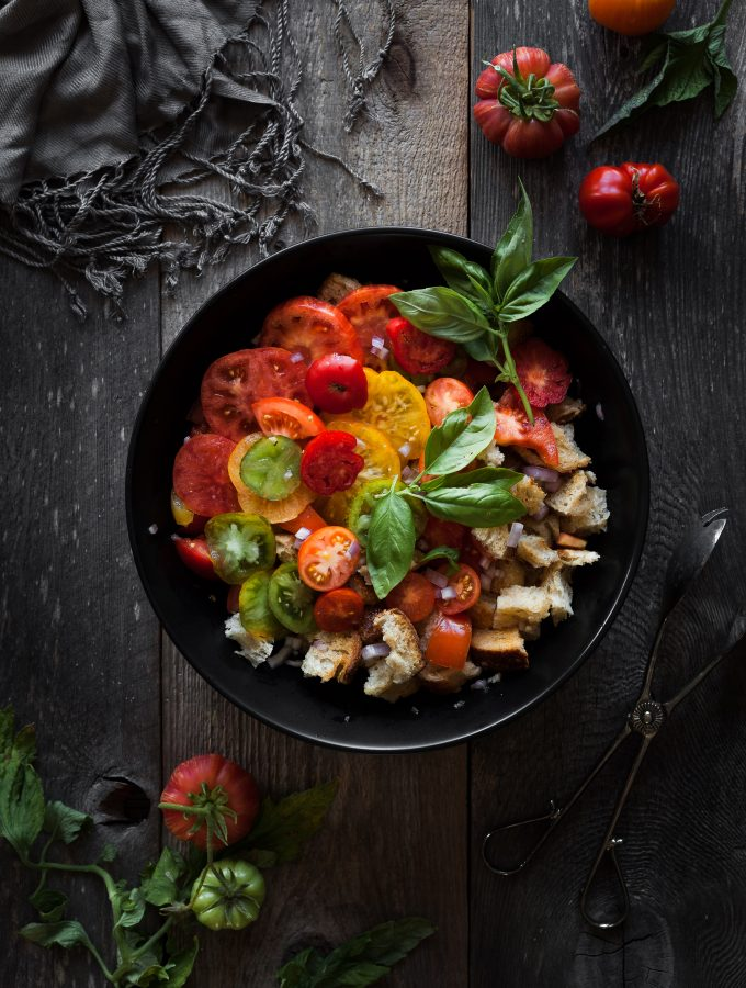 an overhead image of a bowl of panzanella with fresh tomatoes off to the side.