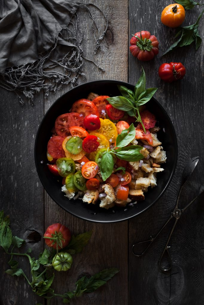overhead view of tomato panzanella with tongs and fresh tomatoes and basil.