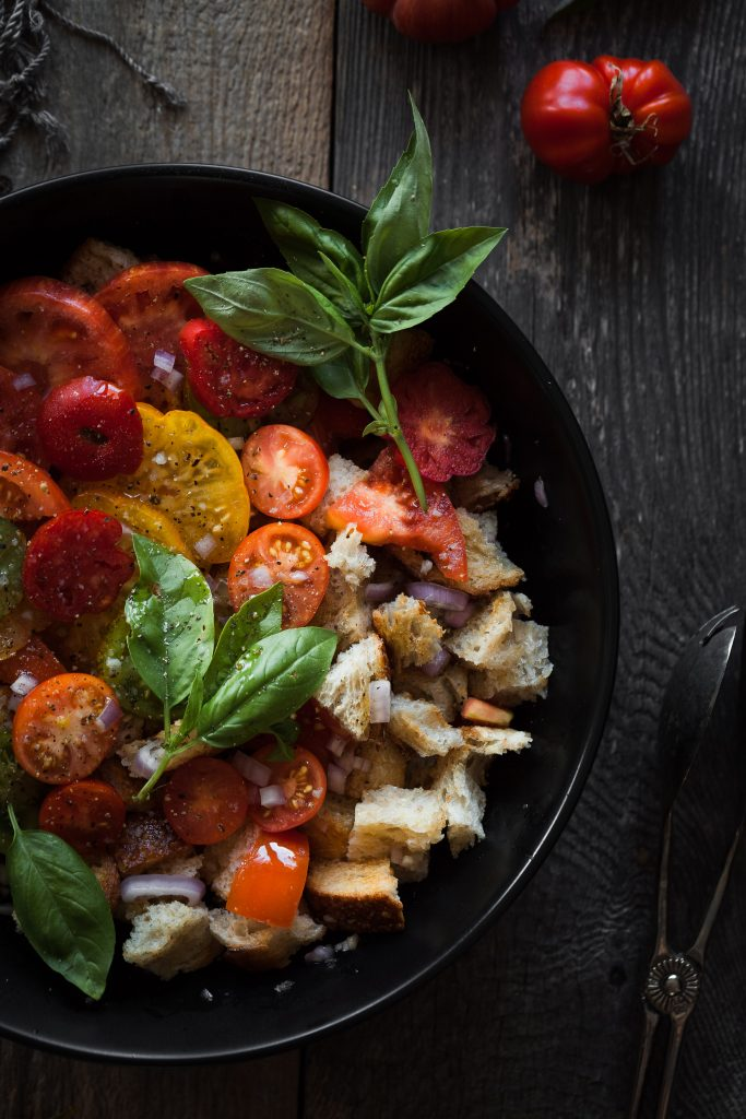 overhead closeup view of a bowl filled with tomato panzanella, salad, basil and tongs.