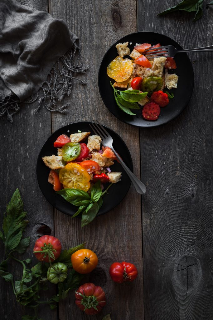 overhead view of two plates of panzanella with forks and tomatoes on a wood surface.