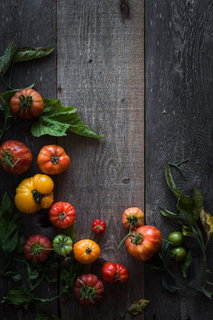 overhead view of heirloom tomatoes and tomato leaves on a wood surface.