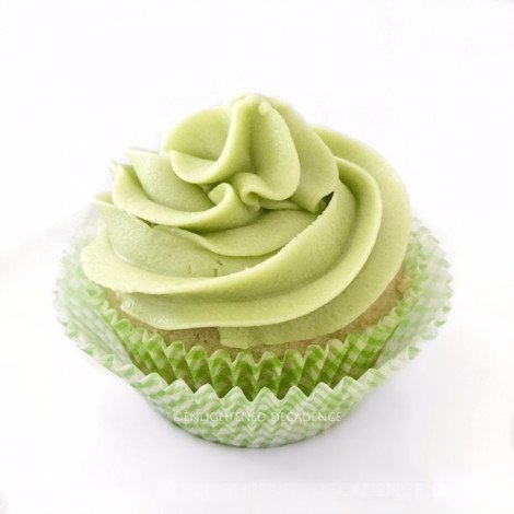 Straight on image of a Matcha Tea Cupcake on a white surface.
