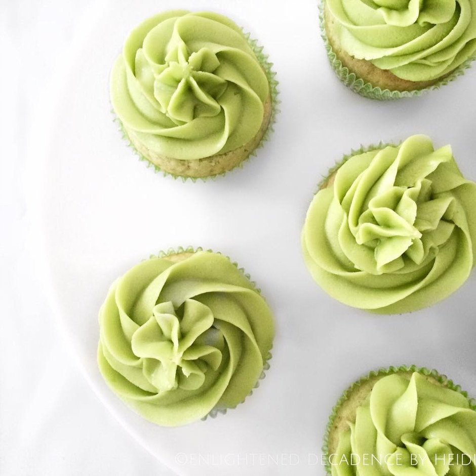 overhead image of 5 forsted matcha tea cupcakes on a white surface.