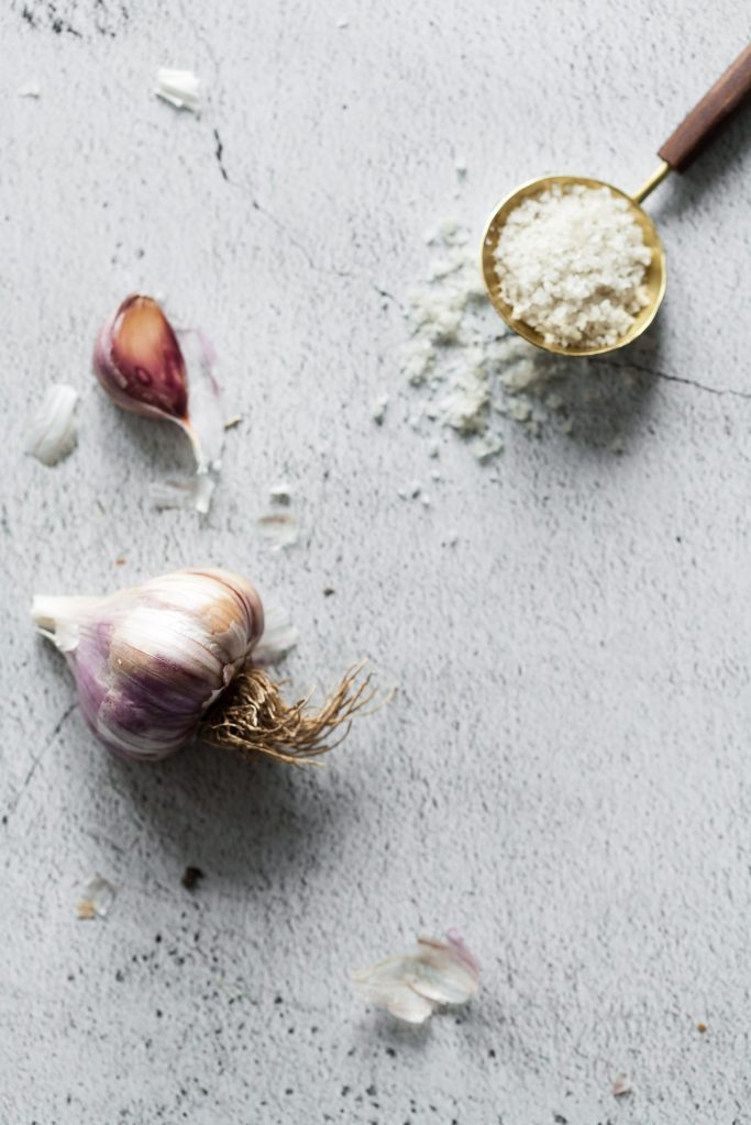 overhead flatlay of a spoon of coarse salt and a head of garlic on a white surface.