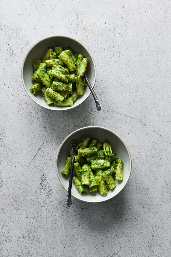 an overhead image of two bowl of pesto pasta on a white stone surface.
