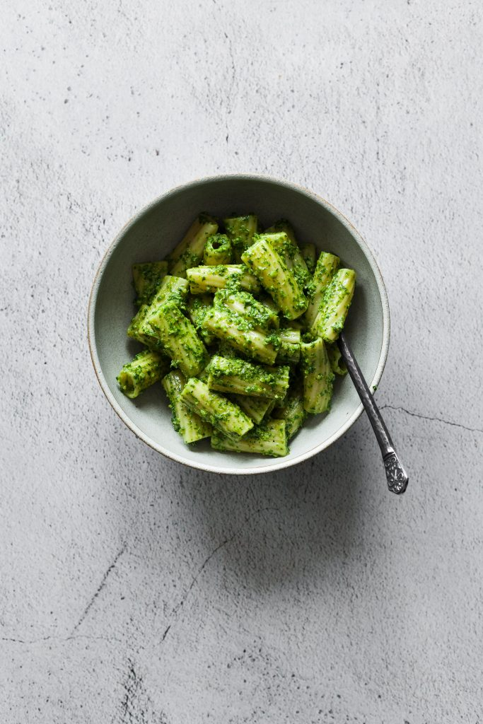 an overhead image of a bowl of vegan parsley walnut pesto on rigatoni noodles on a white stone surface.