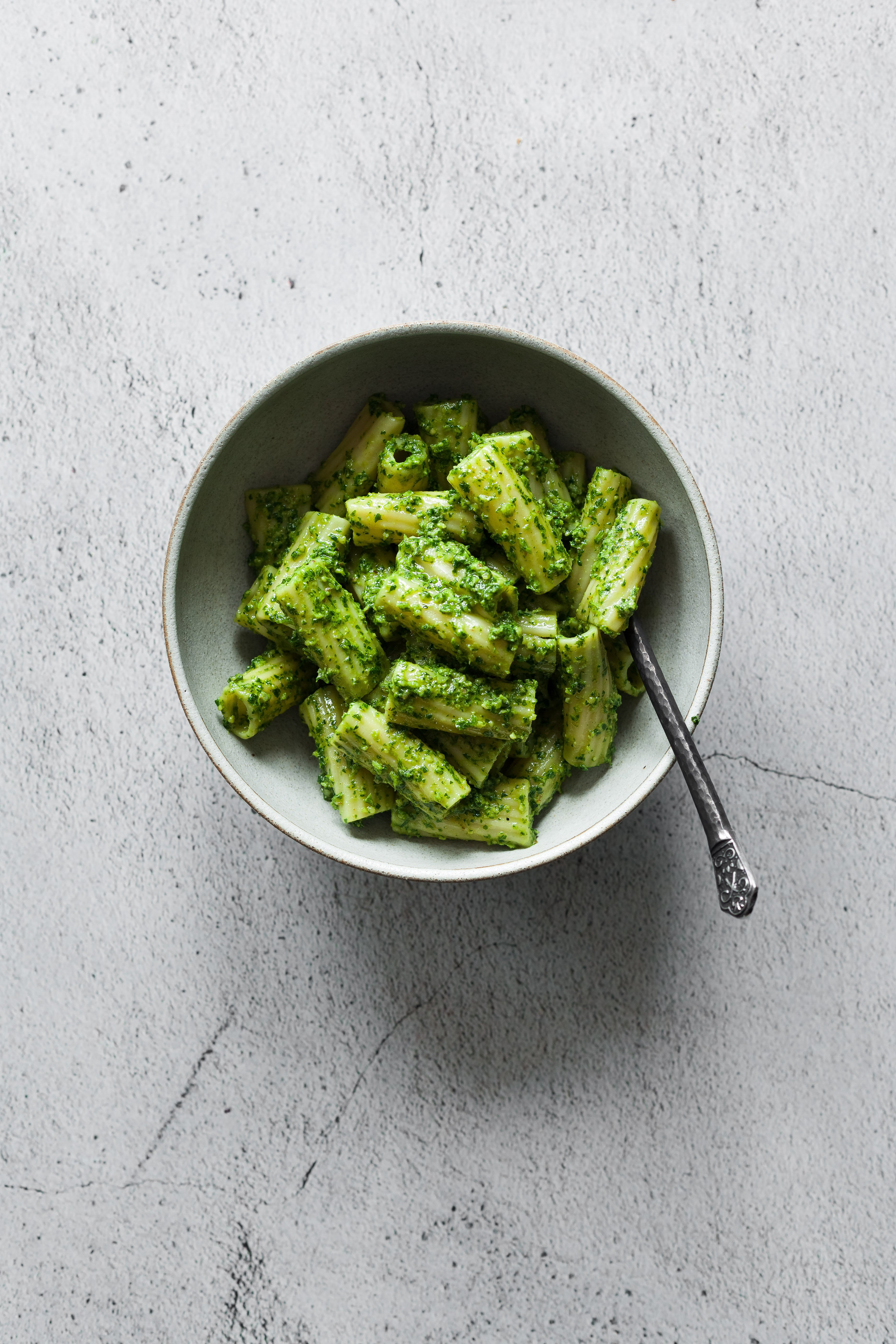 a overhead shot of a bowl of Rigatoni with pesto with a fork.