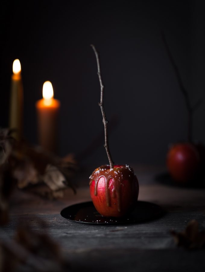 a head on image of a caramel apple on a black plate with candles in the background.