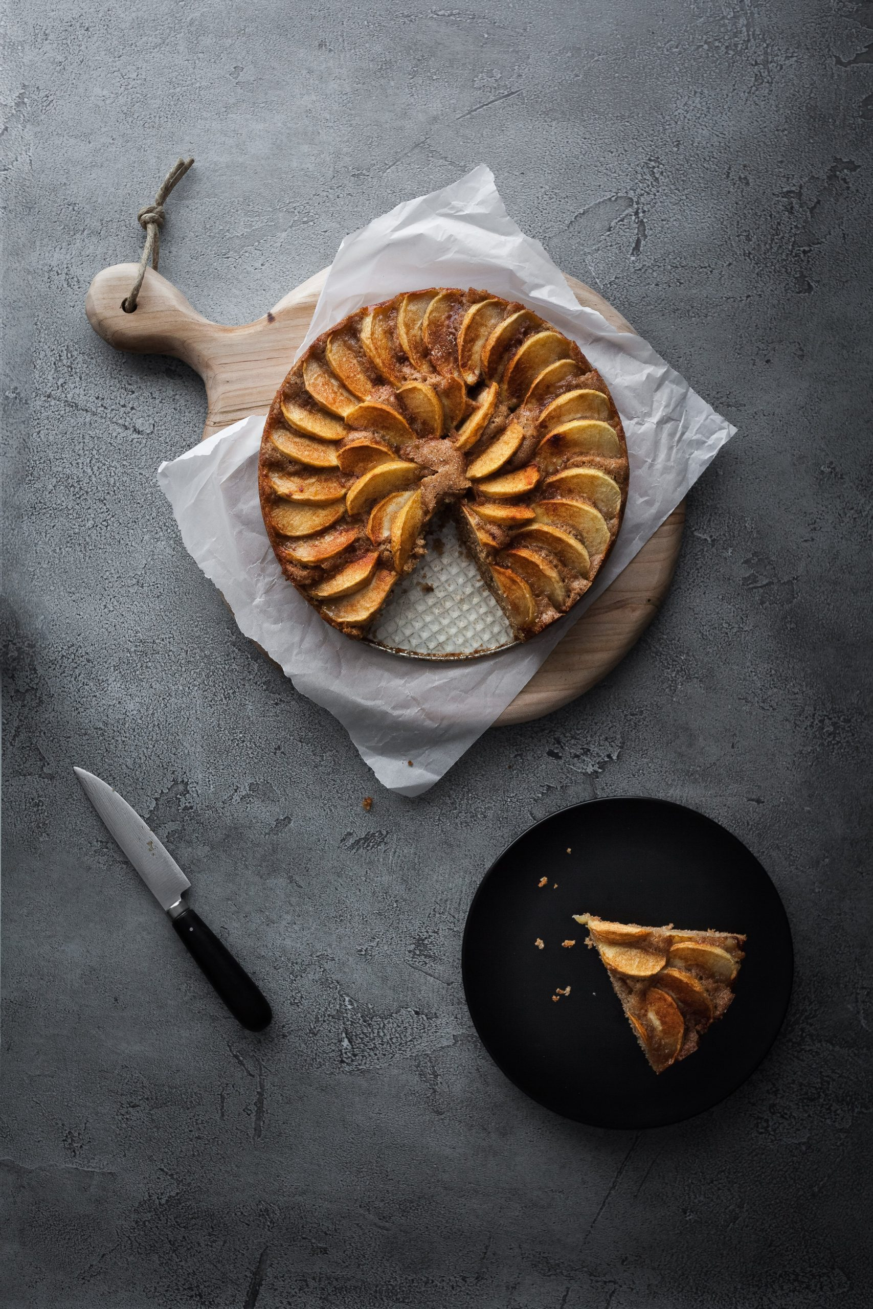 an overhead image of a german apple cake with a slice on a black plate and aknife off to the side.