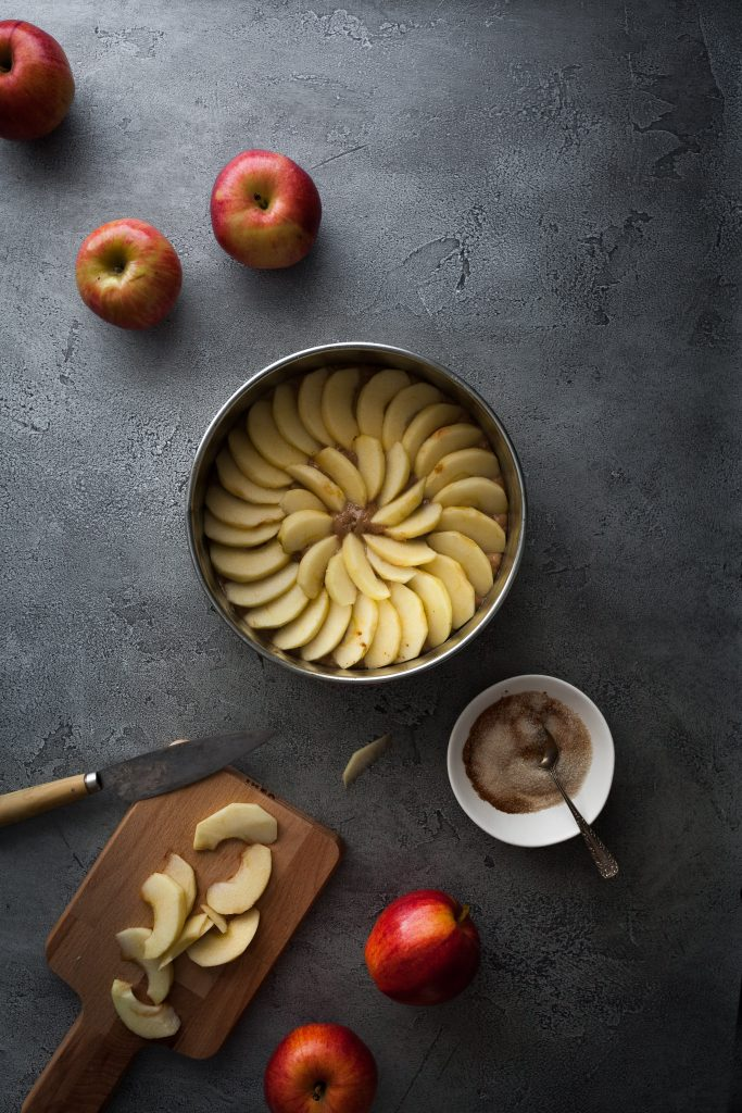 overhead image of a german apple cake with slices of apples on a cutting board and fresh apples on the upper left.