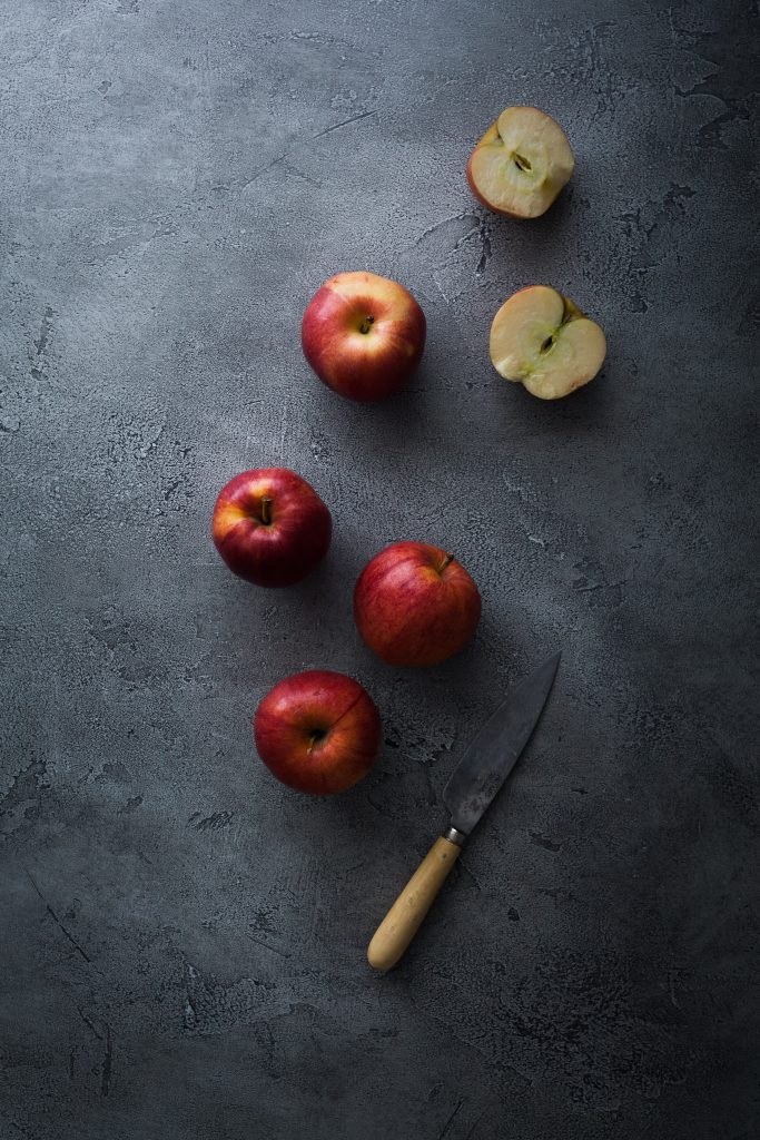 overhead image of apples and a paring knife.