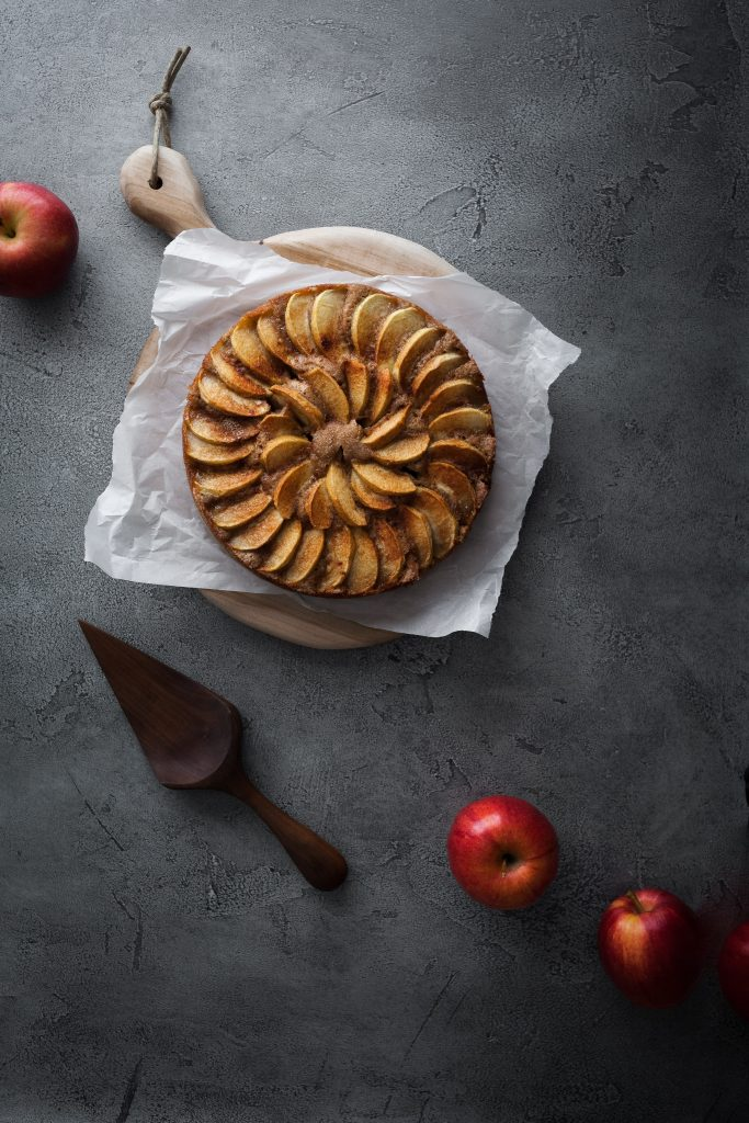 overhead image of german apple cake with cake lifter and 3 fresh apples.