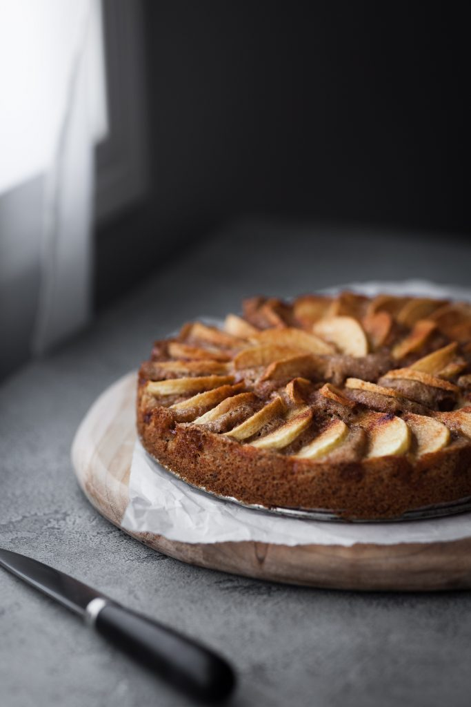 a 3/4 angle view of a vegan german apple cake sitting beside a window with a knife in the foreground.