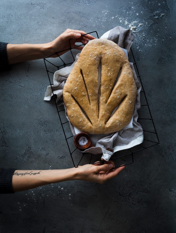 a overhead image of a baker holding a basket of fougasse bread.