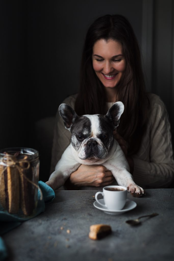 a person sitting with a white french bulldog looking at a piece of biscotti on a table.