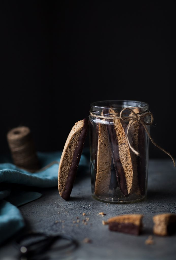 head on image of vegan chocolate olive oil biscotti sitting in a glass jar with a twine bow around it.