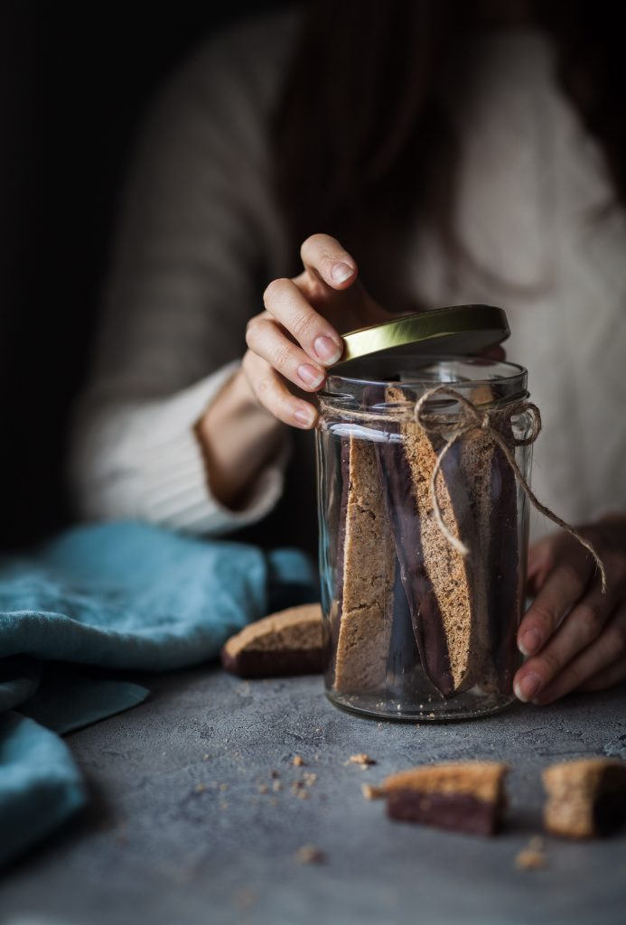 a person opeing a jar of vegan chocolate olive oil biscotti cookies.