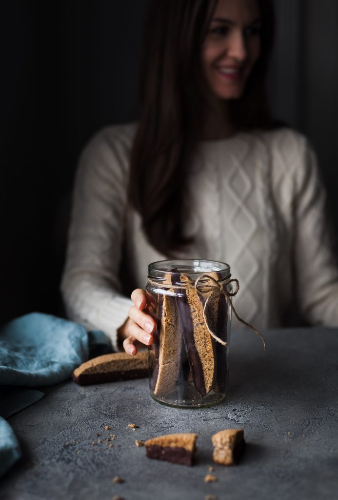 a person holding a jar of vegan chocolate olive oil biscotti with a twine bow on it.