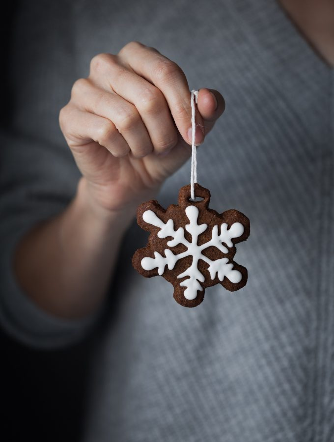 a head on image of an iced gingerbread cookie on a string being held by a baker.