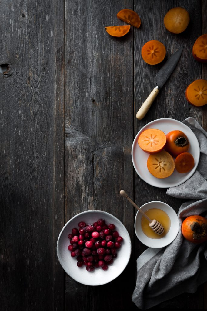 Overhead image of slices persimmons and a bowl of cranberries and honey ssittong on a wood surface.