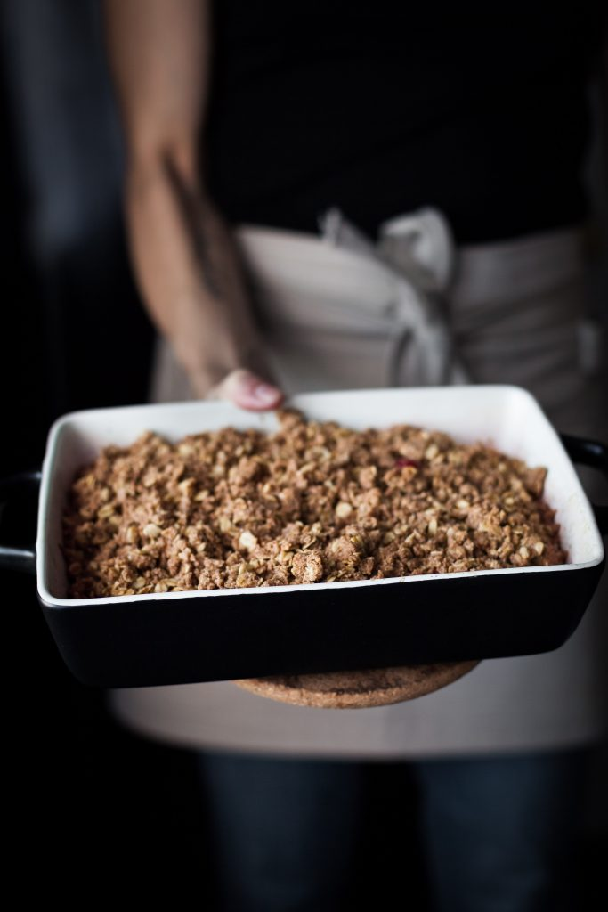 A baker holding a casserole dish of  a Cranberry Persimmon Crisp.