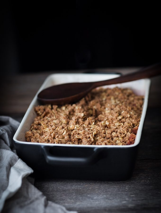 a head on image of a cranberry crisp with a wooden spoon off to the side.