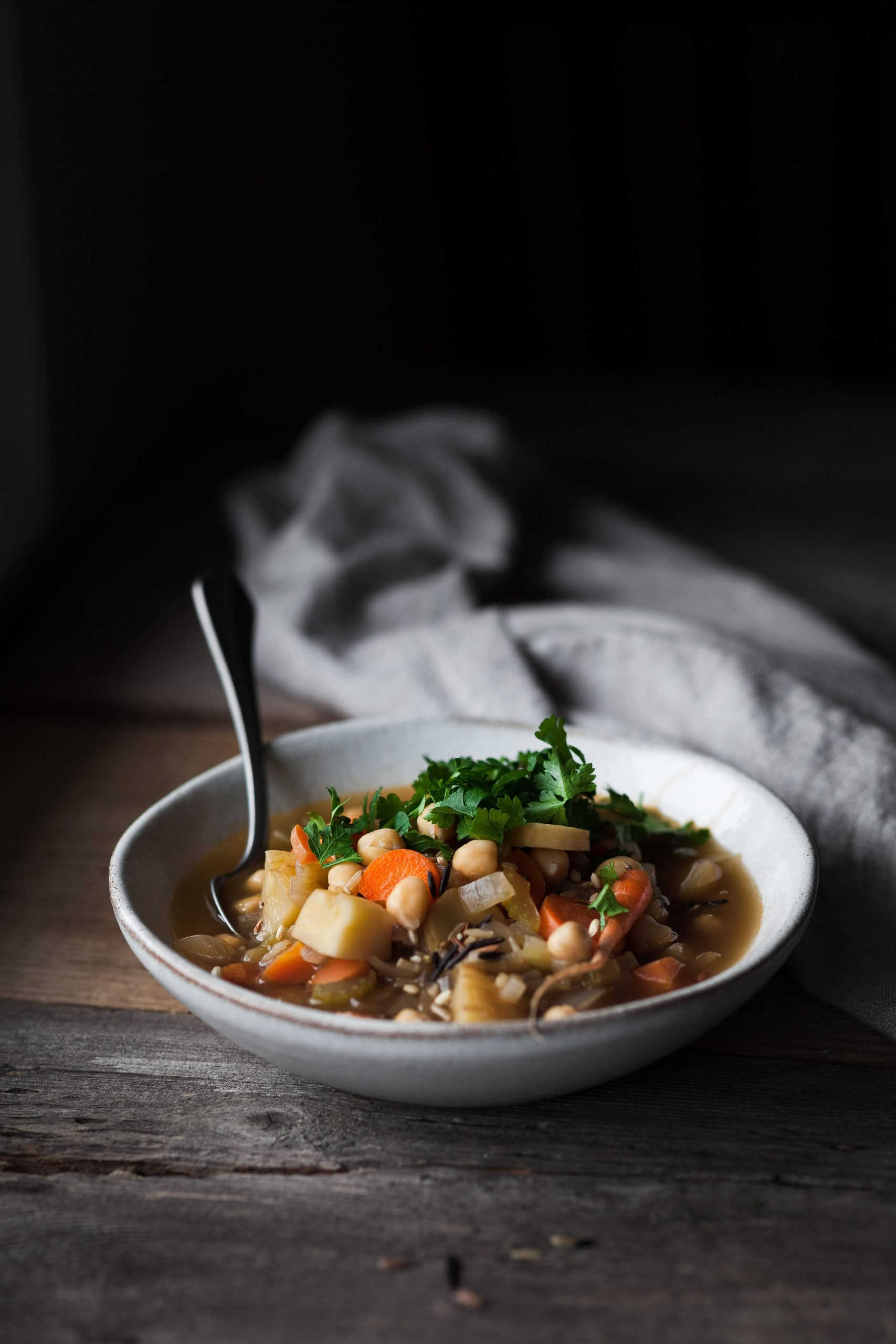 a head on image of a bowl of soup sitting on a wood table.