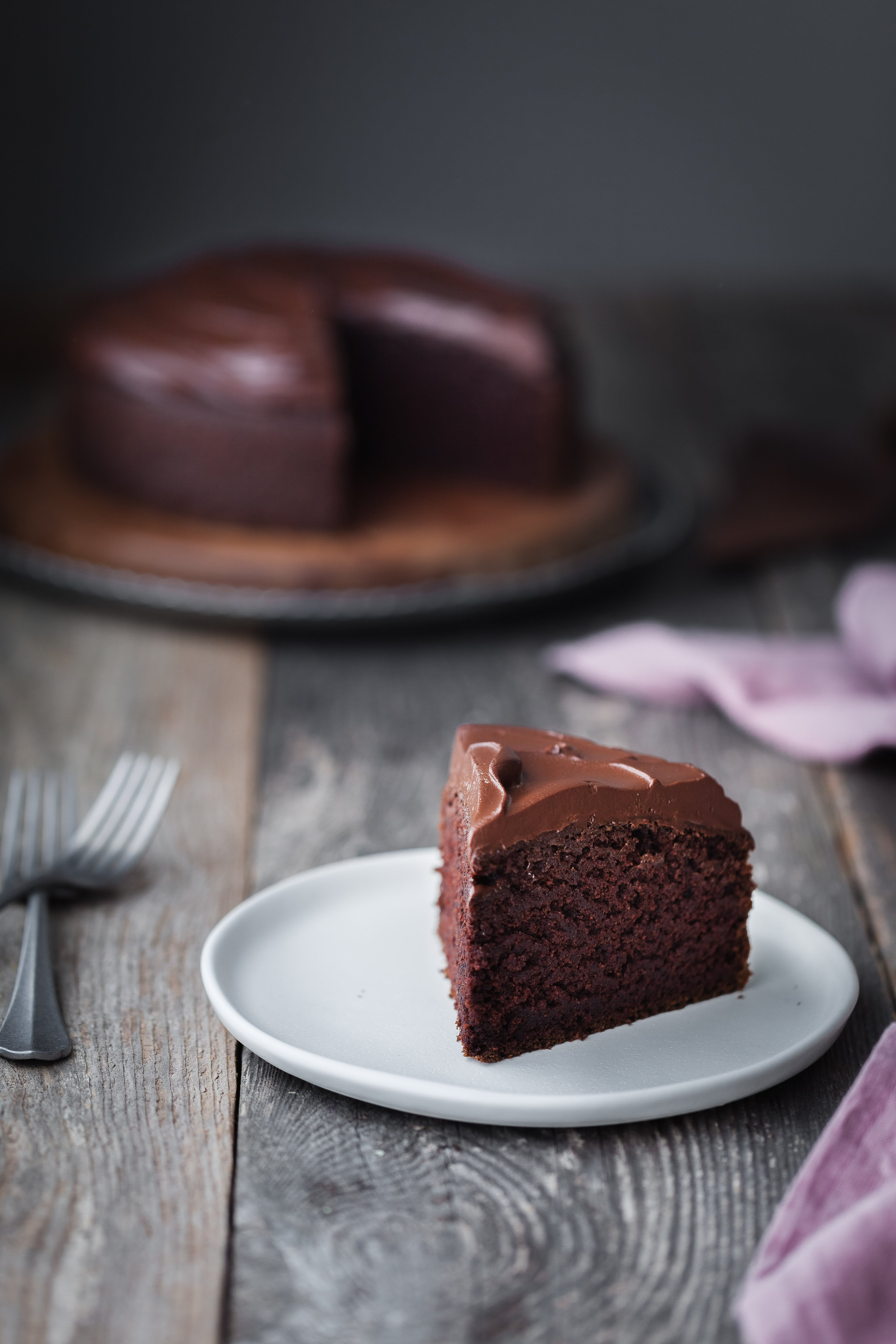 a head on image of a Double Chocolate Beetroot Cake slice on a white plate with a pink linen napkin off to the side.