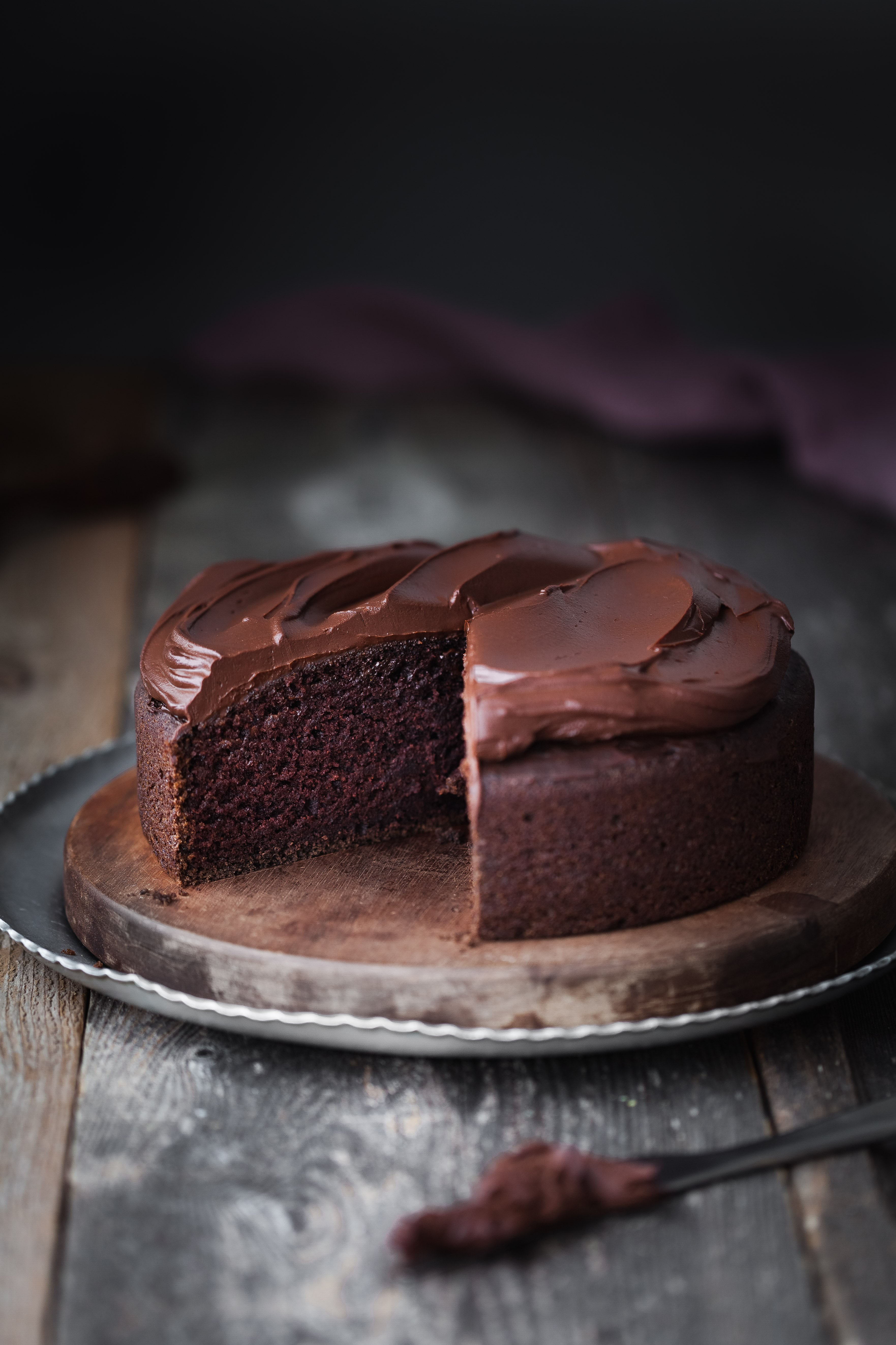 a hea don image of a Double Chocolate Beetroot Cake with a slice removed and a knife in the foreground.
