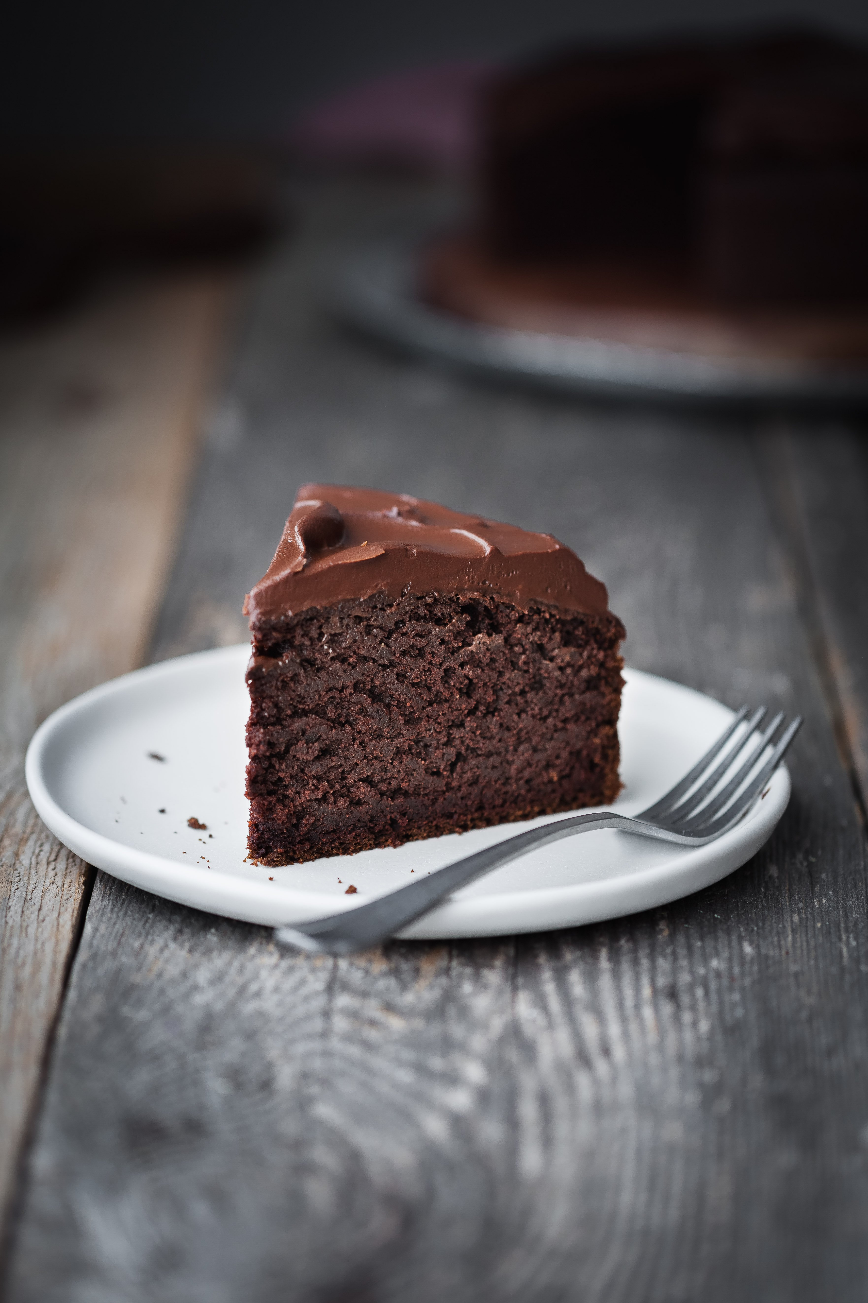 a head on image of a slice of Double Chocolate Beetroot Cake sitting on a white plate on a wood surface.