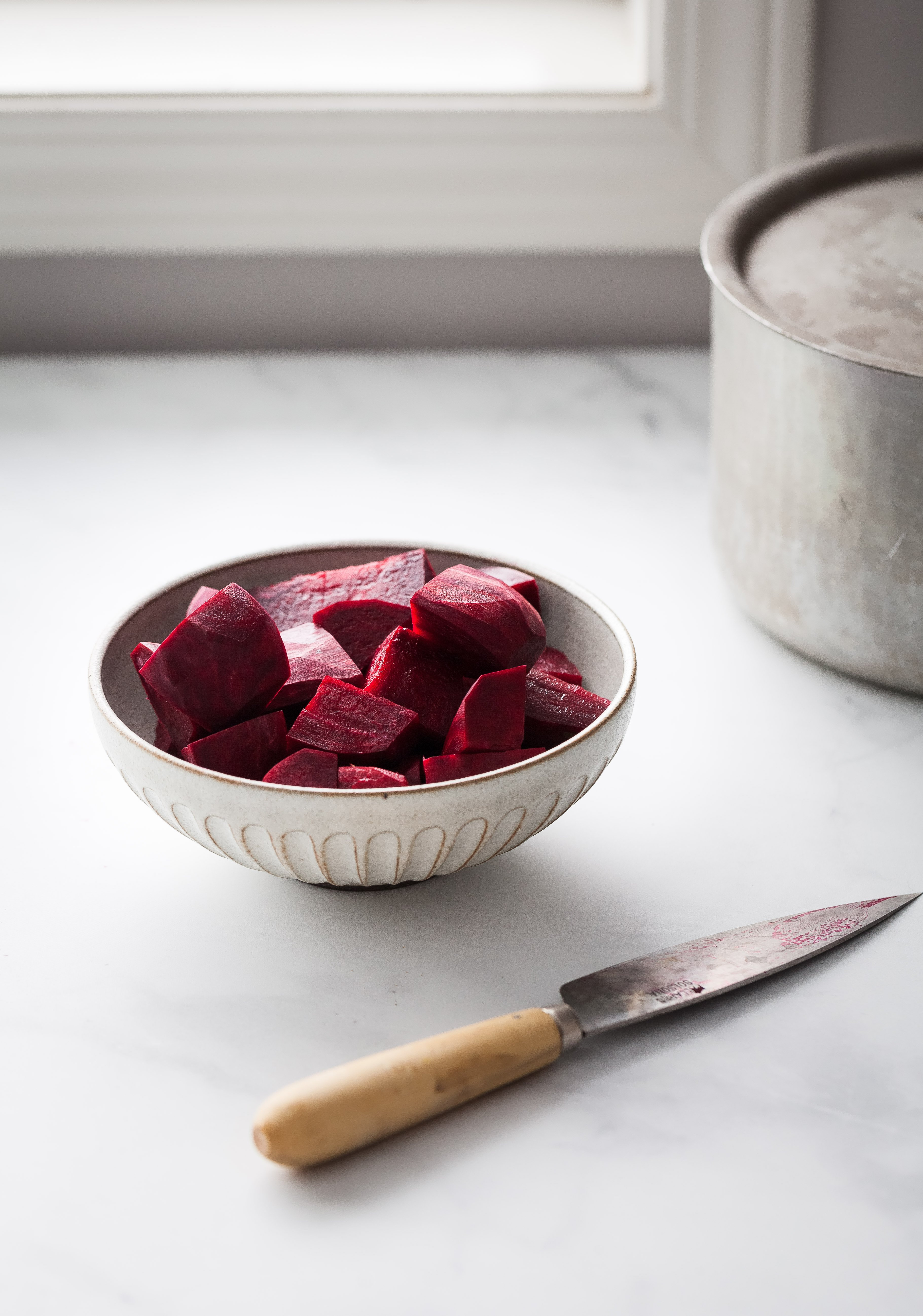 a hea don image of cut up beets sitting in a bowl next to a window.
