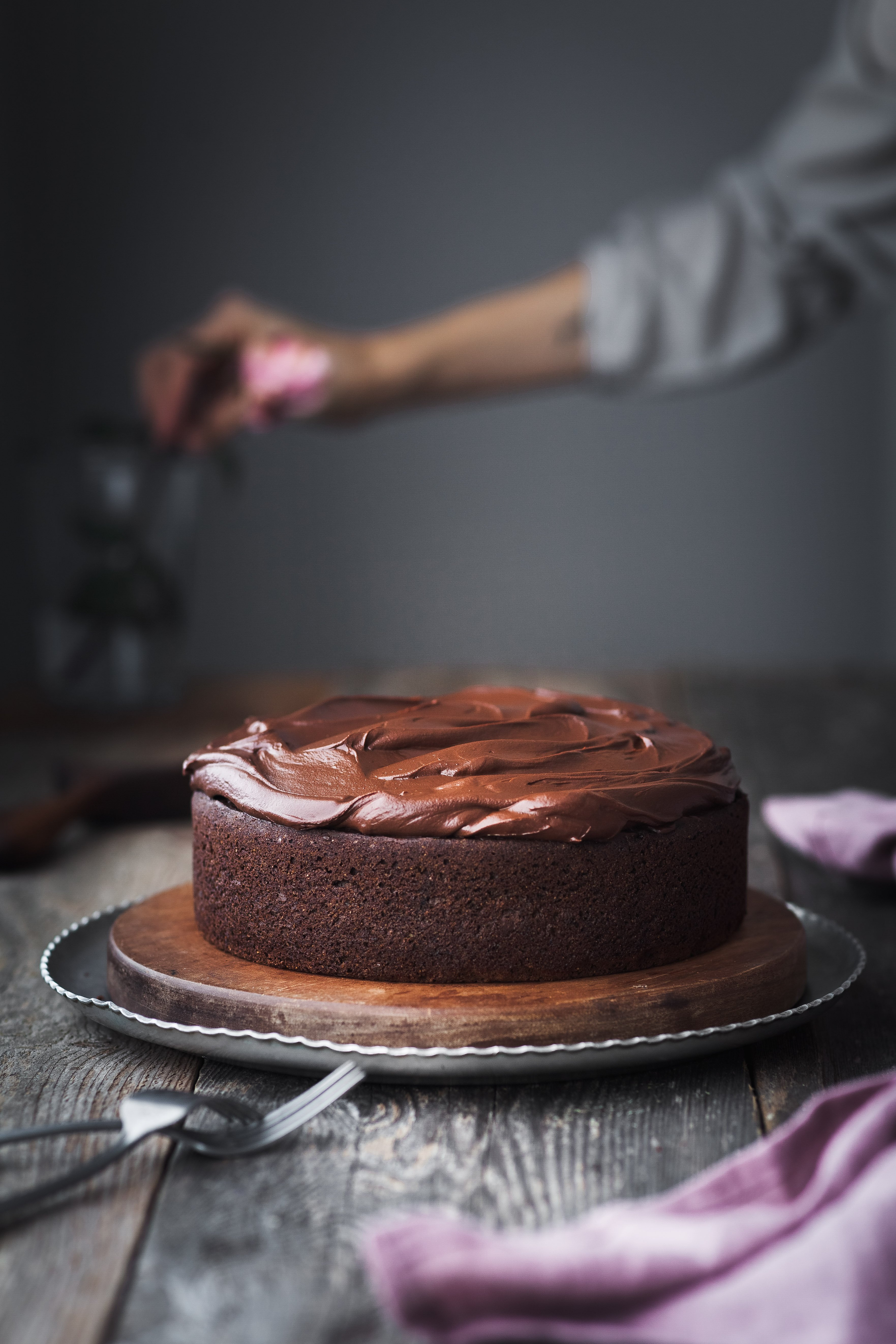 head on image of Double Chocolate Beetroot Cake with a hand in background putting a rose in a vase.