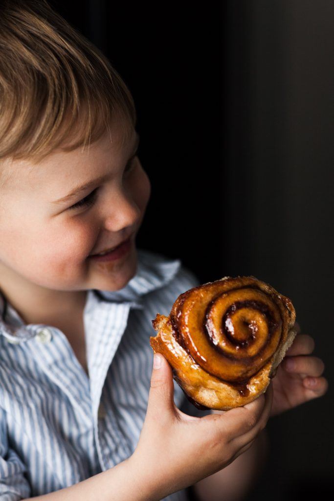 Small child enjoying vegan cinnamon roll.