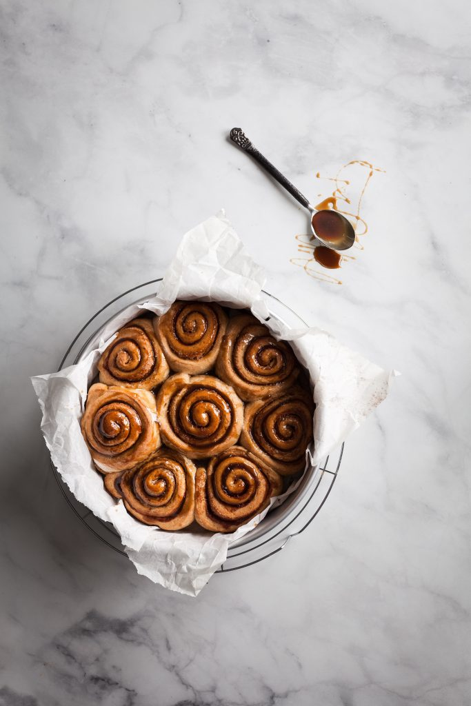 an overhead shot of baked cinnamon rolls with a spoon of sugar glaze on the upper right.