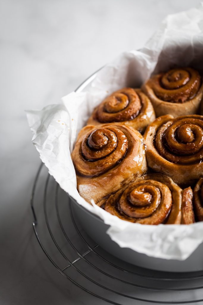 closeup shot of vegan cinnamon rolls in a round baking tin.