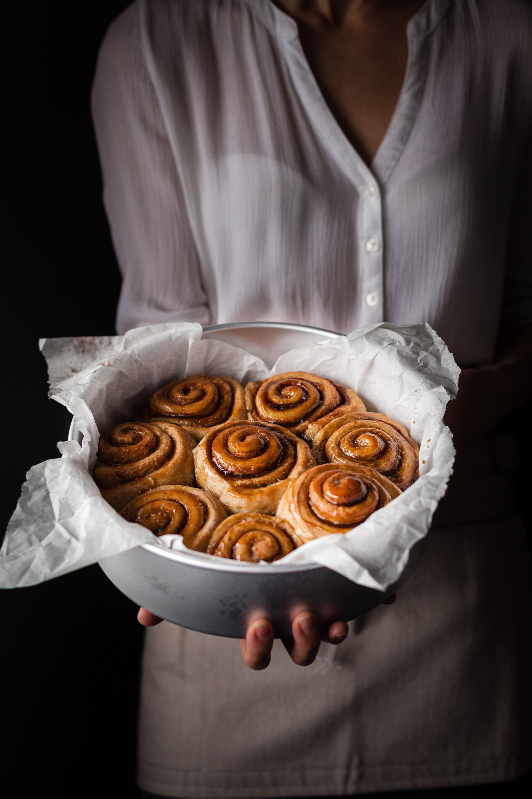 a head on shot of a baker holding a pan of cinnamon rolls.