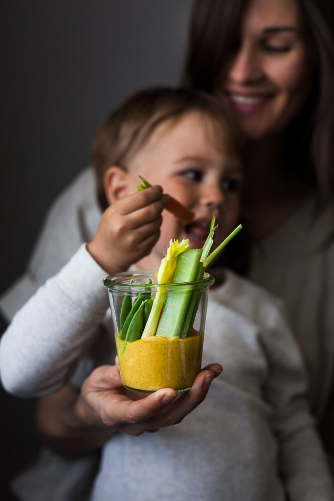 a head on image of a mom and toddler holding a jar of vegetables and golden dip.