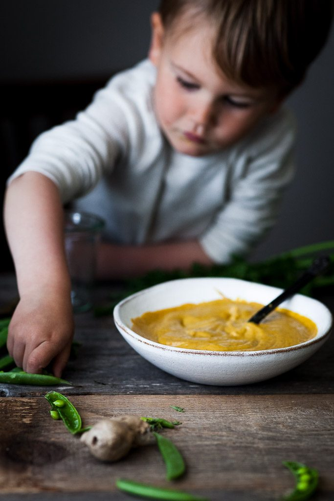 A head on image of a child reaching for peas with a bowl of dip off to the side.