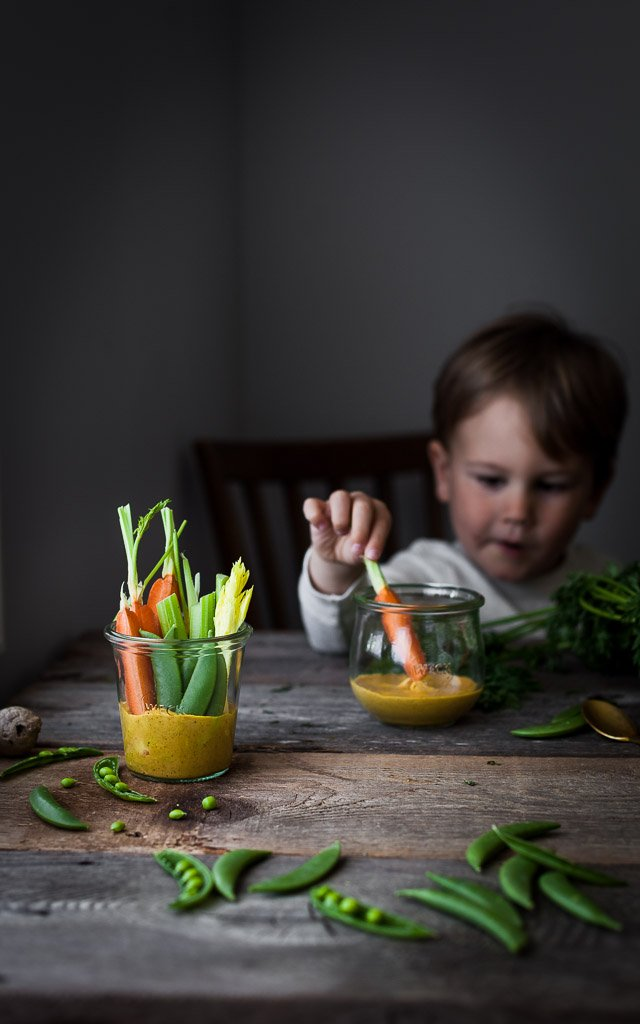 A head on image of a child dipping veggies in a jar of dip.