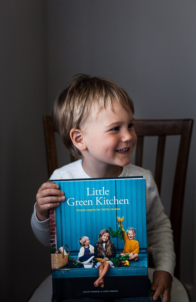 "A head on image of a child holding the cookbook ""Little Green Kitchen"""