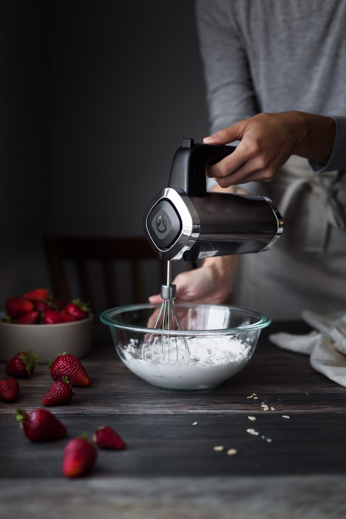 a person whipping coconut cream with a hand mixer. and a bowl of strawberries to the left.
